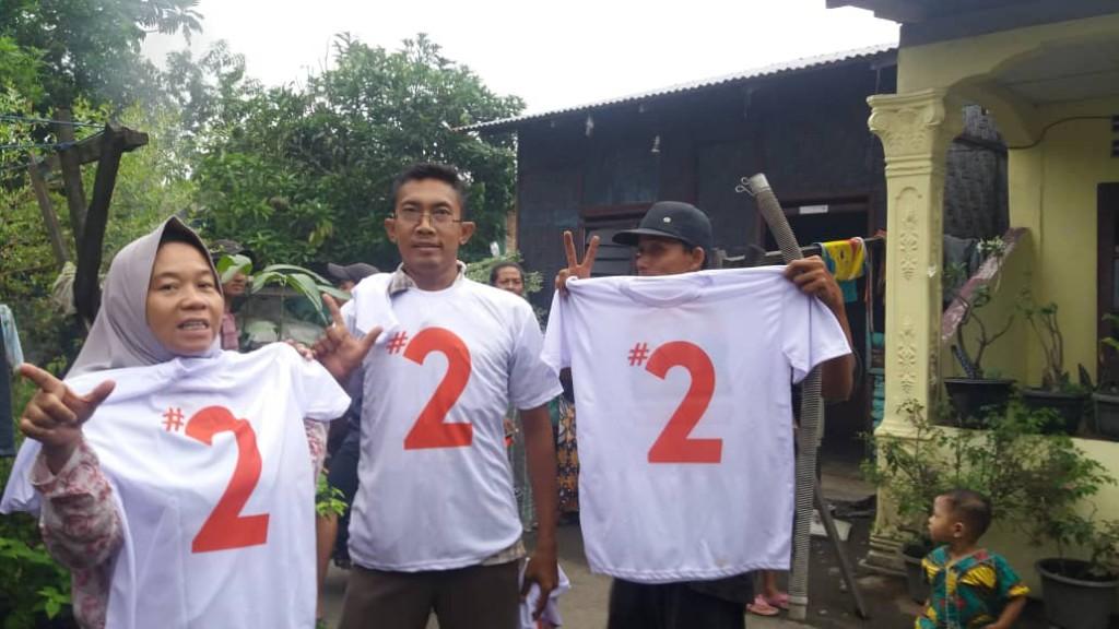 3 orang relawan Bobby dan Aulia menunjukan baju bernomor 2 menunjukkan bahwa mereka mendukung